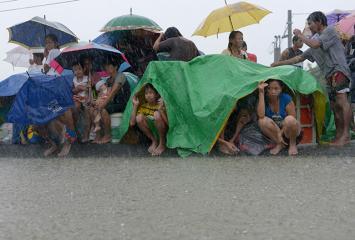Cavite residents flee flooded homes, take shelter on street