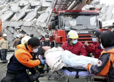 Rescue personnel help a victim at the site where a 17-storey apartment building collapsed during an earthquake in Tainan, southern Taiwan. REUTERS