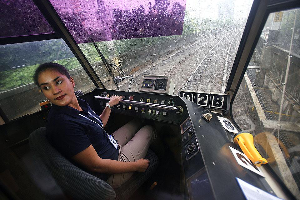 Kathleen dela Paz, the 26-year-old female driver hired by the Light Rail Manila Corporation, sites behind the controls of an LRT train on her first day on the job Tuesday, August 9, 2016. Photo by Danny Pata