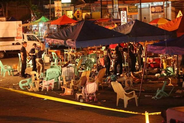 Police investigators collect evidence through injured and dead people lying on the ground, at the site of an explosion at a night market in Davao City on September 2, 2016. AFP/Manman Dejeto