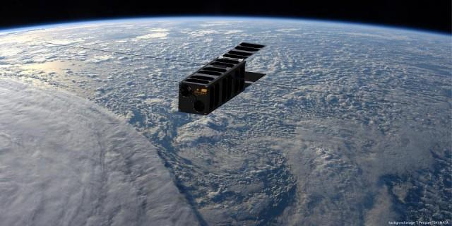 This handout artist's impression released by Lesia/Observatoire de Paris-PSL on January 10, 2018 shows the PicSat nano-satellite in orbit around the Earth with a background image by Thomas Pesquet released by the ESA. Handout/LESIA/Observatoire de Paris-PSL/AFP