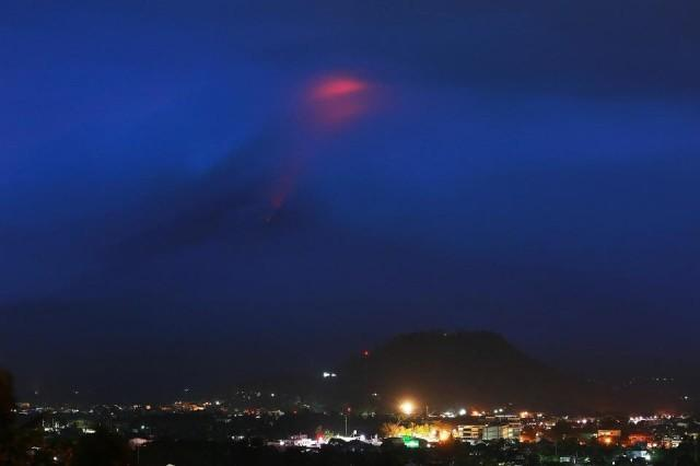The glow of lava from the cloud-covered Mayon Volcano as it erupts is pictured from Legazpi, Albay early on January 15, 2018. Simvale Sayat/AFP