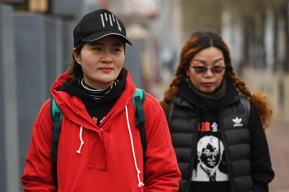 Li Wenzu (L), the wife of detained human rights lawyer Wang Quanzhang, walks with supporter Lin Ermin (R), the wife of rights activist Zhai Yanmin, who was sentenced to a suspended three-year prison sentence in August 2016, on the outskirts of Beijing on April 5, 2018. Li is walking walking 100 kilometers from Beijing to Tianjin, where she believes her husband is being held, to demand answers about his fate, in an unusual case that has sparked international outcry. Greg Baker/AFP