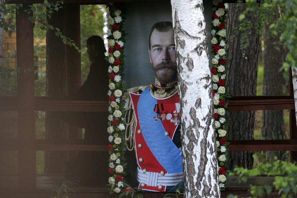 A Russian Orthodox priest walks close to a portrait of the last Russian tsar, Nicholas II on July 17, 2018. Vlad Lonshakov/AFP