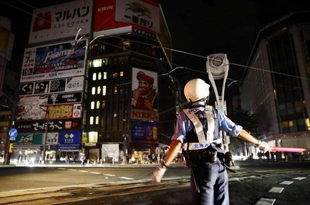 A police officer is seen during blackout after a powerful earthquake hit the area at a cross-point in Sapporo, Japan in this photo taken by Kyodo September 6, 2018. Mandatory credit Kyodo/via REUTERS