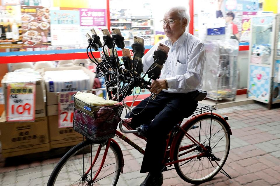 """Taiwanese Chen San-yuan, 70, known as """"Pokemon grandpa,"""" plays the mobile game Pokemon Go with 15 mobile phones in New Taipei City, Taiwan November 12, 2018. REUTERS/Tyrone Siu"""