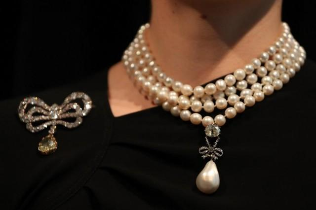 """In this file photo taken on October 19, 2018 a model wears Marie Antoinette's Pearl, with an estimated value of $1 million to $2 million, on the French queen's pearl and diamond necklace, together with her diamond brooch during a photocall for """"The Royal Jewels from the Bourbon Parma Family"""" at Sotheby's auction house in London on October 19, 2018. One of the most important royal jewelry collections ever to come to auction comes for sale at Sotheby's in Geneva on November 14, 2018. The auction will span centuries of European history, from the reign of Louis XVI to the fall of the Austro-Hungarian Empire. Daniel Leal-Olivas/AFP"""