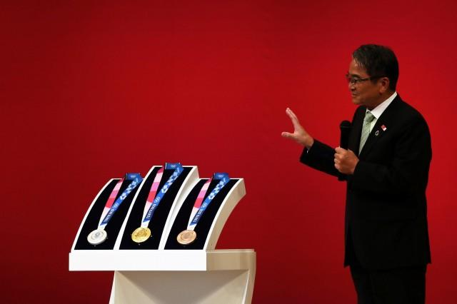 The medals for the Tokyo 2020 Olympic Games are unveiled as Ryohei Miyata, commissioner for cultural affairs and Tokyo 2020 medal design competition panel chair, speaks during a ceremony marking one year before the start of the games in Tokyo on July 24, 2019. AFP
