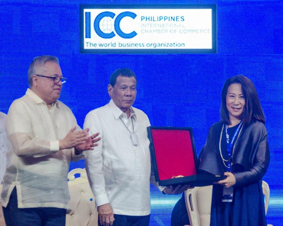 SM Hotels and Conventions Corporation President Elizabeth T. Sy receives on behalf of her father and SM founder Henry Sy Sr. the posthumous award from the International Chamber of Commerce Philippines. With her on stage are (from left) Trade Secretary Ramon M. Lopez and President Rodrigo R. Duterte. SMIC