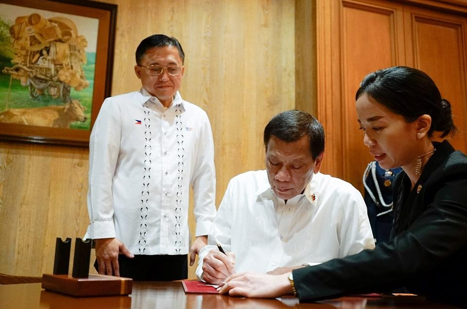 President Rodrigo Duterte signs the Salary Standardization Law into effect as his ever-present former assistant Senator Bong Go looks on. Photo: Office of the President