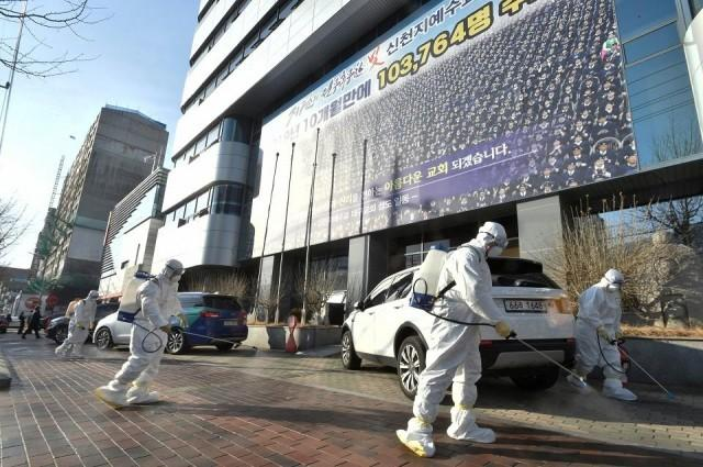 """Workers from a disinfection service company sanitize a street in front of a branch of the Shincheonji Church of Jesus the Temple of the Tabernacle of the Testimony where a woman known as """"Patient 31"""" attended a service in Daegu, South Korea, February 19, 2020. Yonhap via REUTERS"""
