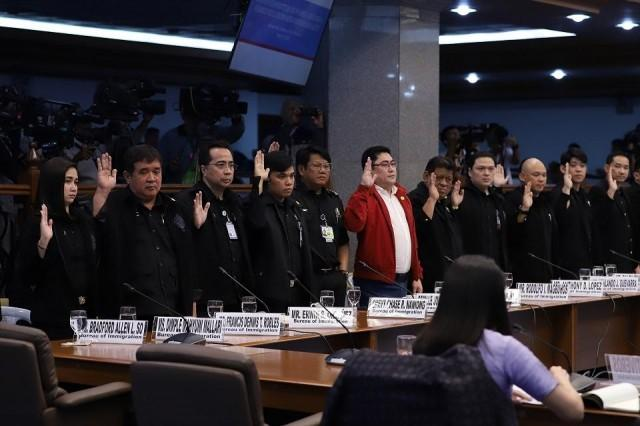 Bureau of Immigration officers including former Immigration Port Operations Division (POD) chief Marc Red Mariñas (in red) swear to tell the truth during a public hearing on the human trafficking in the Philippine Offshore Gaming Operators (POGOs) industry Monday, March 2, 2020. Joseph Vidal/Senate PRIB