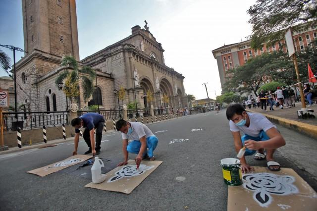 Staff members of the Manila Cathedral inside Intramuros, Manila stencil markers on the pavement for social distancing on Saturday, ahead of the start of the traditional Simbang Gabi. DANNY PATA