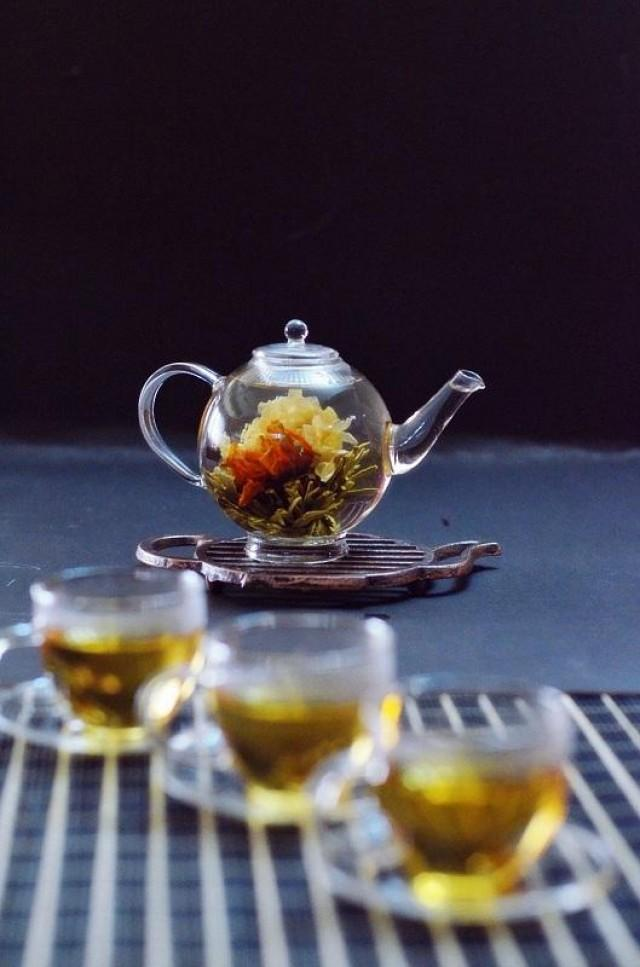 """One of their bestsellers, the blooming tea is literally a work of art. Flower buds are handpicked and tied with green, black, or white tea buds. When the tea is steeped in a cup of hot water, the bud opens up into a beautiful """"blossom."""""""
