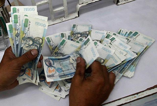 Money changer counts P1,000 bills in Manila